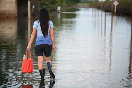 Ragazza che cammina sulla strada allagata, portando acqua fresca per bere Archivio Fotografico - 21491946