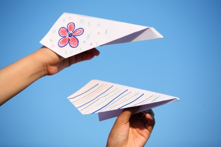 hand holding paper airplane with blue sky  photo