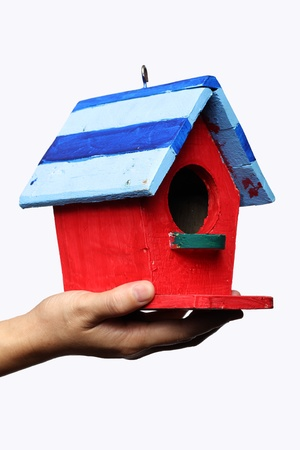 hand holding colorful bird house isolated on white background  photo