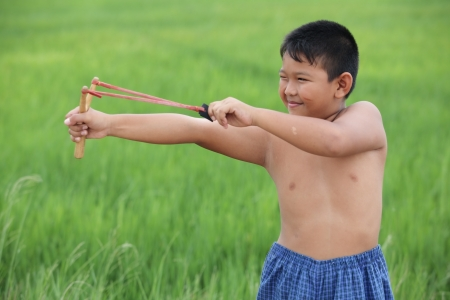 young boy using slingshot  photo
