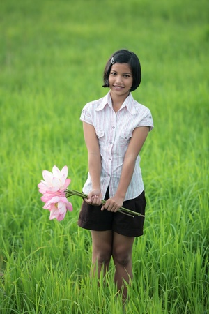 girl with lotus flower in paddy field  photo