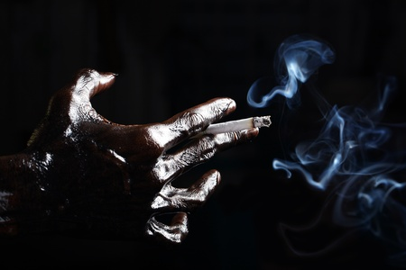 dirty hand with cigarette isolated on black background  photo