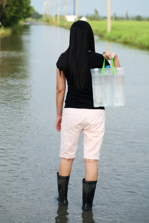 girl walking on flood street,carrying fresh water for drinking photo