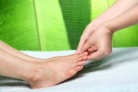 foot massage with green background. photo