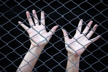 prison bars: hand in jail