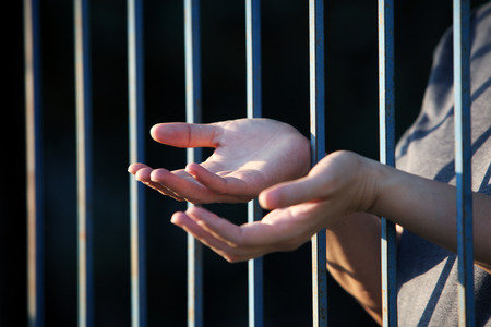 handcuffed hands: hand praying in jail