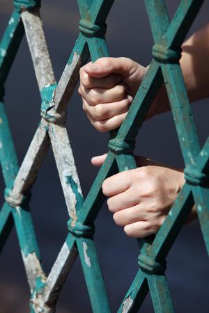 behind bars: hand behind bars
