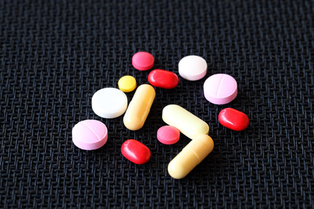 antibiotic pink pill: colorful pills on black background. Stock Photo