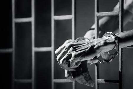 hands of prisoner in jail as background.