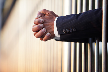 law suit: hand of businessman in jail as background with copyspace.
