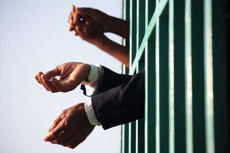 hands of business man locking with handcuff in jail as background.