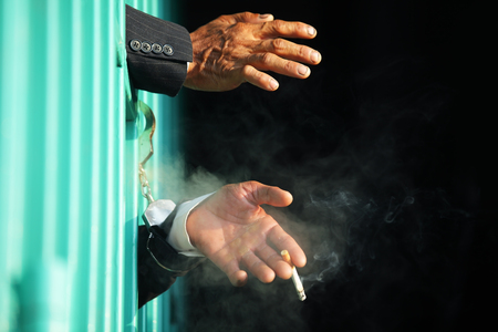 hand of business man smoking cigarette in jail with black background.
