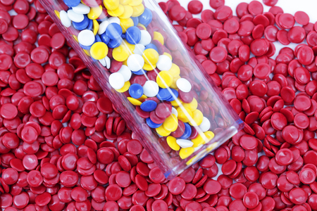 thermoplastic: Colorful plastic polymer granules in test tube with red granule background.