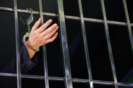 trapped: hand in jail with handcuff as background.