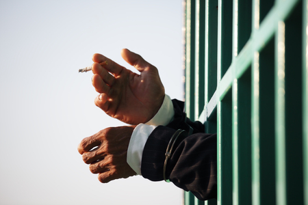 law suit: hands of business man locked with handcuff smoking cigarette in jail with copyspace. Stock Photo