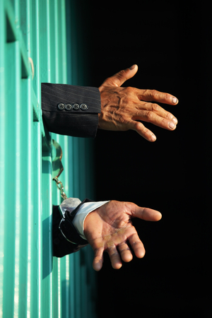 hands of businessman in jail Stock Photo