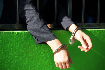 close up portrait of  business woman in handcuffs. hands in jail with crime concept