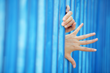 woman hands in jail with blue copyspace as background.