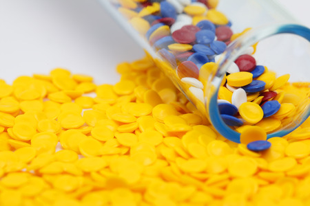 Colorful plastic polymer granules in test tube with yellow granule background. Stock Photo - 81370349