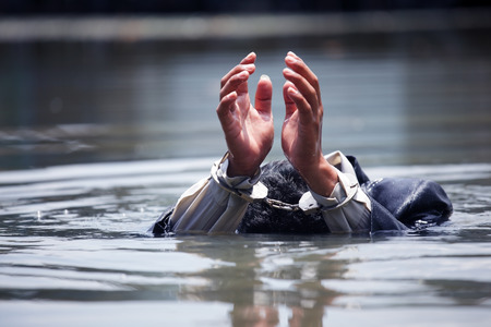 sink: businessman was arrested by handcuffs and drowning in water with copyspace. Stock Photo