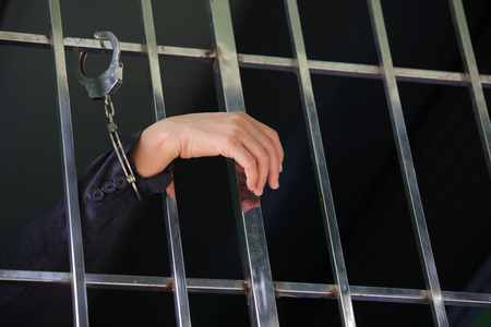 hands arrested by handcuff in jail as background. Stock Photo