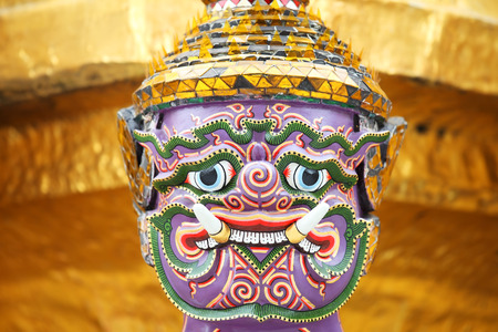mask of demon which support golden chedi(ramayana saga) with golden background.