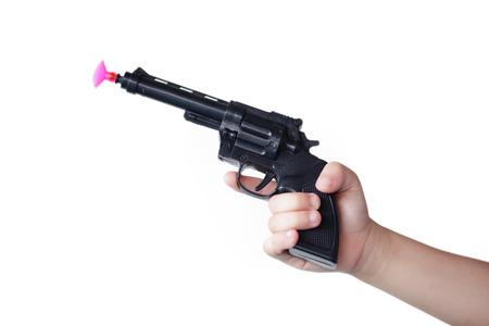 흰색 배경에 고립 장난감 총을 들고 어린이의 손.