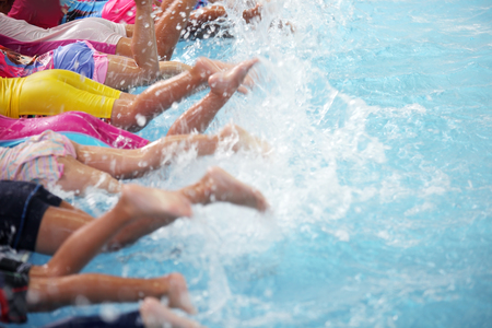 group of children at swimming pool class learning to swim Banco de Imagens