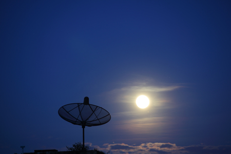 Parabolic satellite dish in twilight time with blue sky cloud and moon on supermoon night(3 december 2017).