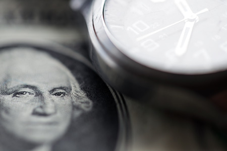 Close up of us dollar note and watch background. Stock Photo