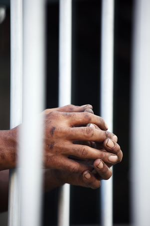 hand of prisoner in jail background. Stock Photo - 94033379