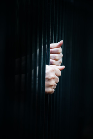 close up hands of prisoner in jail background. Stock Photo - 96208529