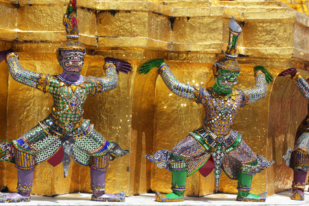 colorful mosaic glass demon statue which support tradition golden chedi at bangkok royal grand palace,THAILAND. Banco de Imagens