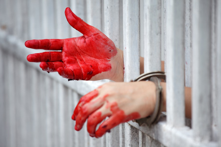 bloody hand of murderer in jail background.