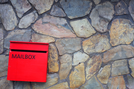 red mailbox with stone wall background.