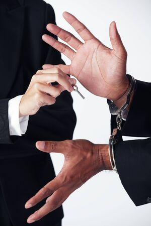 businessman using key to release businessman locked with handcuff. 스톡 콘텐츠