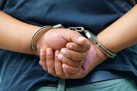 arrested man in handcuffs with hands behind Stock Photo