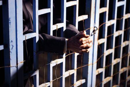 Nahaufnahme der Hände des Geschäftsmannes im Gefängnis.