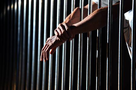 close up of prisoner hands in jail background