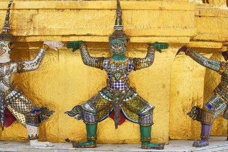 colorful tradition demon statue which support golden pagoda Imagens