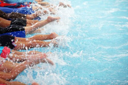 leg shot of group of Kids kicking splashing water as they are learning to swim in the pool active healthy lifestyle Stok Fotoğraf