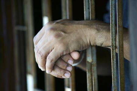 Joined wrinkle Hand Shot of an old male prisoner behind the bars  Banco de Imagens