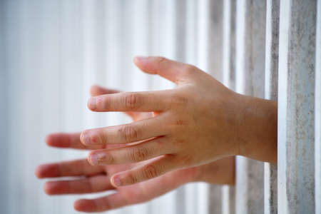 close up of prisoner hand in jail Standard-Bild