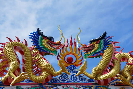 dragon statue on roof against blue sky