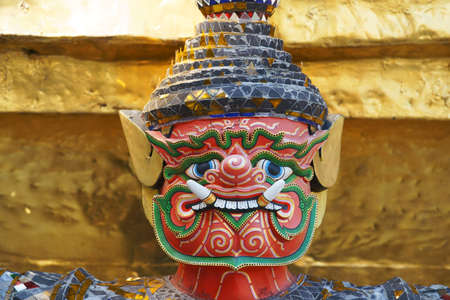 mask of colorful tradition demon statue which support golden pagoda in grand royal palace,wat Pra Kaew Bangkok,thailand. Stock Photo