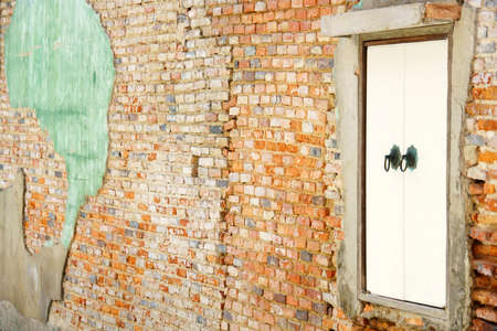 old crack red brick wall background with wooden vintage window
