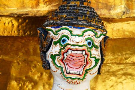 head of ramayana statue with golden pagoda background at wat phra kaew,grand royal palace Bangkok,THAILAND.