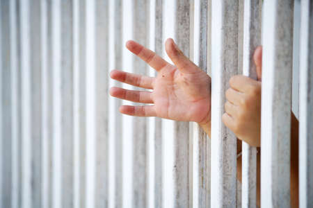 close up of prisoner hand in jail Stock Photo