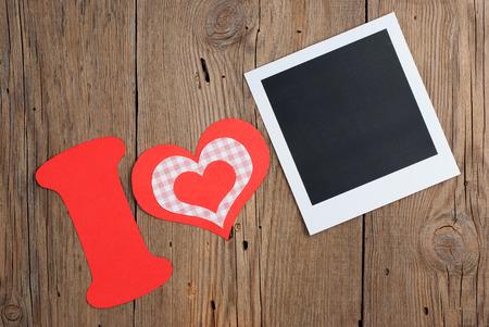 papier a lettre: Instant photo et lettre de papier avec des coeurs formant la phrase Je AIME sur le vieux fond en bois