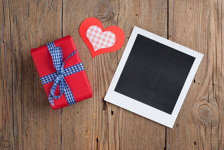 Instant photo with gift and paper hearts on old wooden background photo